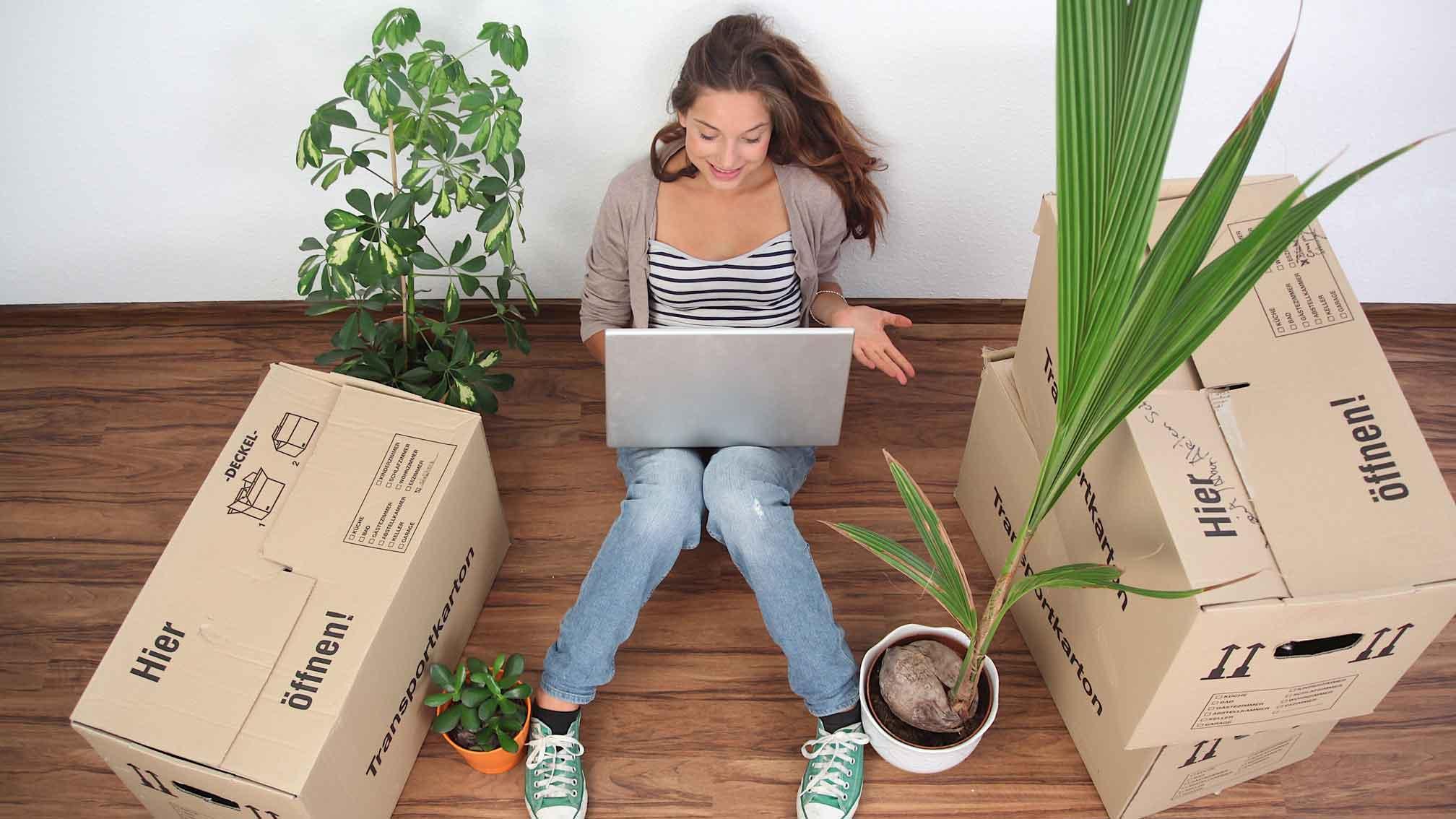 Junge Frau sitzt mit Laptop auf dem Boden.